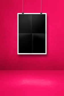 Black folded poster hanging on a pink wall with clips. blank mockup template