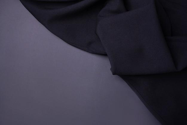Черные складки ткани на темном фоне. концепция черной пятницы