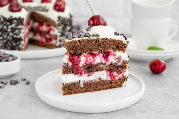 黒い森のケーキ、シュヴァルツヴァルトのパイ。灰色のコンクリートの背景にダークチョコレート、ホイップクリーム、チェリーのケーキ。スペースをコピーします。