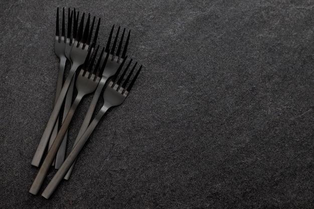 灰色のセラミックの背景に黒いフォーク