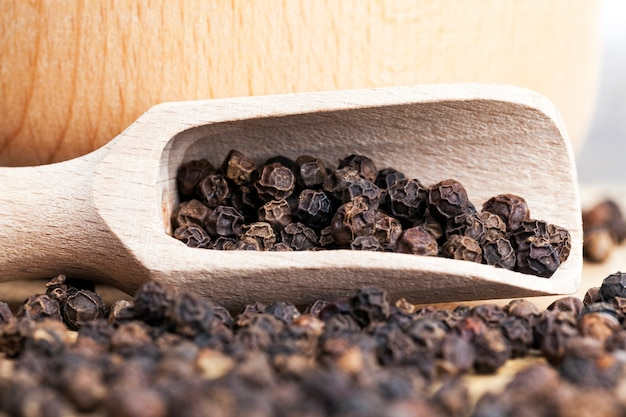 Black fragrant pepper with a wooden spoon, cooking with hot spices, closeup