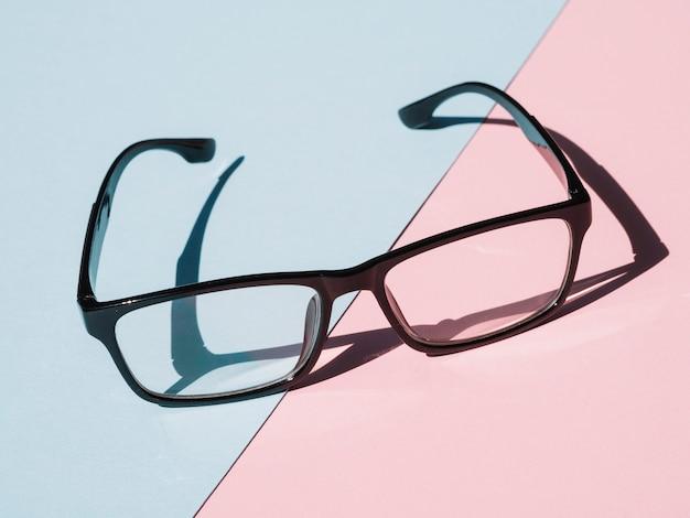 ピンクと青の背景に黒のフレーム眼鏡