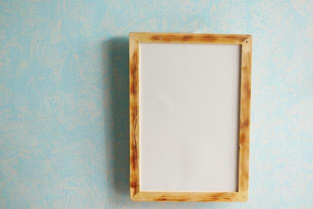 Black frame mockup on table against white wall