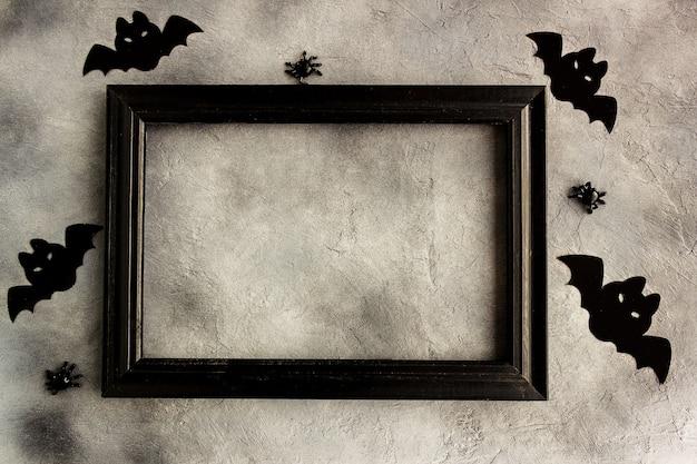 회색 배경에 검은색 프레임, 종이 박쥐, 거미, 현대적인 최소한의 디자인.