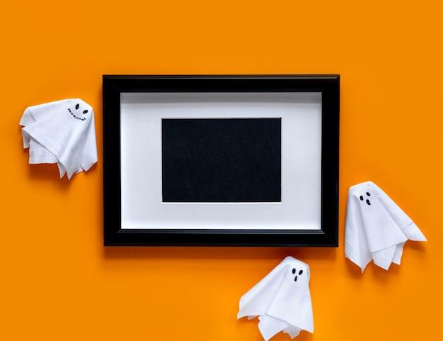 Черная рамка с привидениями на оранжевом фоне. плоская планировка, вид сверху.