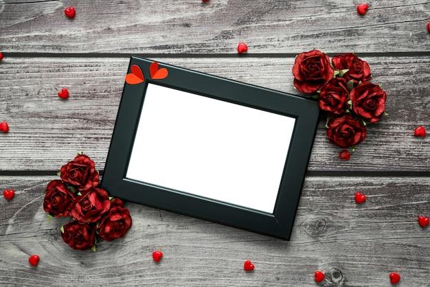 Черная рамка с сердечками и розами на винтажном деревянном фоне с copyspace для текста. вид сверху на тему валентина.