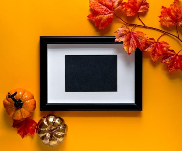 Черная рамка с кленовыми ветвями и декором из тыквы на оранжевом фоне. осенняя концепция. место для текста.