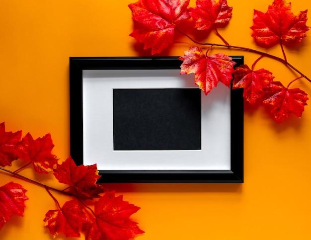 Черная рамка с кленовыми ветвями на оранжевом фоне. осенняя концепция. место для текста.