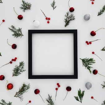 Black frame with patterns made with pine leaves, and decorative christmas balls