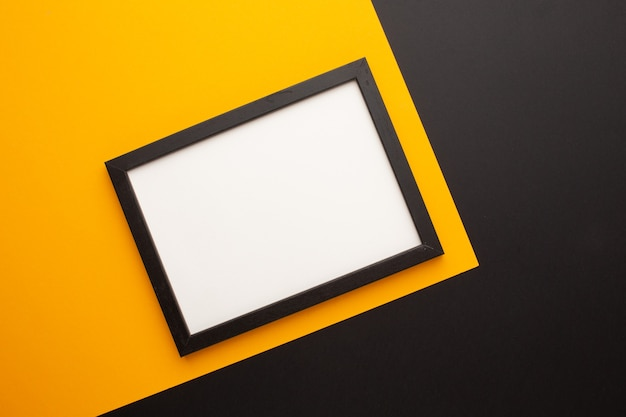 Black frame on a yellow and black background with a place for an inscription. high quality photo