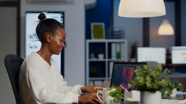 Черный разработчик игр-фрилансер печатает на клавиатуре, развивая новый уровень видеоигр. африканский профессиональный игрок тестирует игру на уровне интерфейса в полночь из делового офиса с помощью ноутбука.