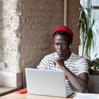 黒人のフリーランサーの男性が、カフェでノートパソコンのリモートオンライン作業のウェビナーを見ながらワイヤレスヘッドフォンを着用します