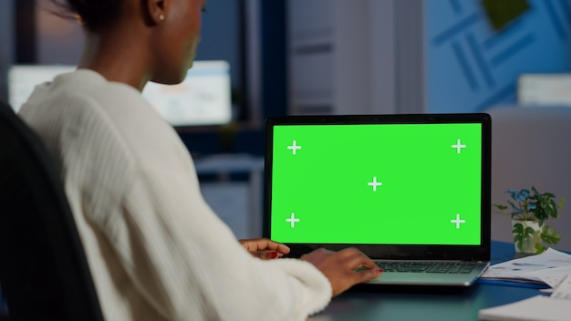 Black freelancer searching using laptop with greenscreen display