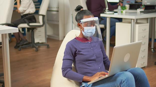 코로나바이러스에 대한 보호 마스크를 쓴 흑인 프리랜서는 랩톱에서 프로젝트를 분석하는 직장 사무실 방 한가운데에 앉아 있습니다. 사회적 거리를 존중하는 다민족 비즈니스 팀