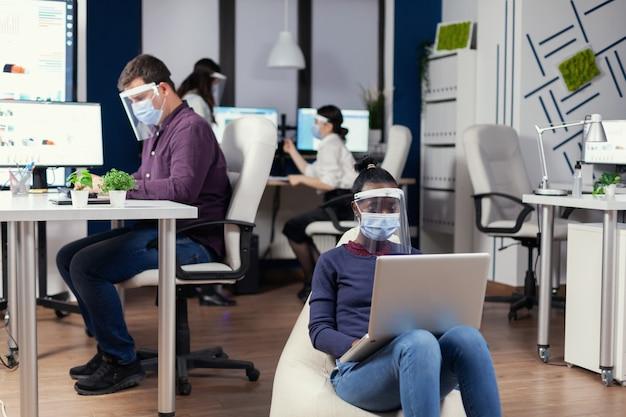디지털 태블릿에서 프로젝트를 분석하는 사무실 한가운데 안락의자에 앉아 코로나바이러스에 대한 보호 마스크를 쓴 흑인 프리랜서. 사회적 거리를 존중하는 다민족 비즈니스 팀