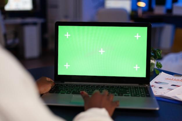 Черный фрилансер, работающий на ноутбуке с зеленым экраном, зеленым макетом, рабочим столом с цветным ключом, сидит за столом в бизнес-офисе и работает ночью