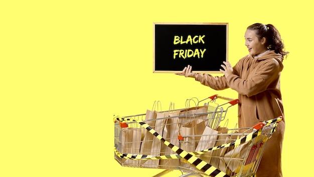 ブラックフライデー、買い物袋でいっぱいのカートの横に立っている女の子が看板を持っています