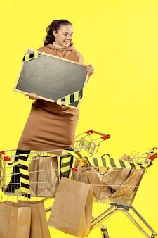 검은 금요일. 한 소녀가 쇼핑 카트에 서서 복사할 곳이 있는 표지판을 들고 있습니다.