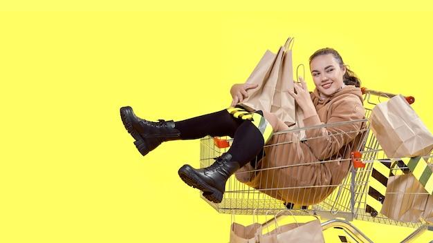Черная пятница, девушка сидит в корзине для покупок и радостно обнимает сумки для покупок.
