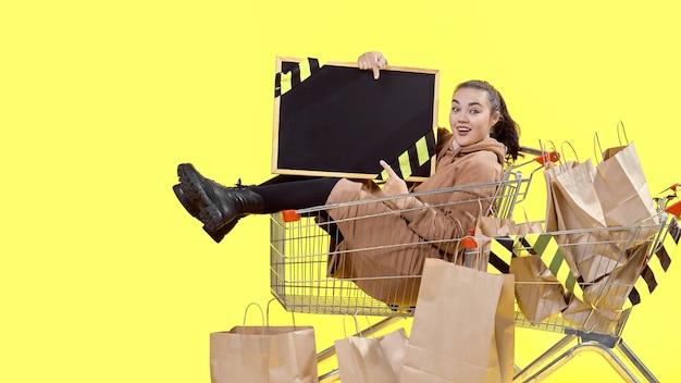 Черная пятница, девушка сидит в корзине для покупок и радостно указывает на доску в руках.