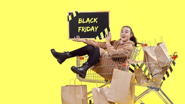 블랙 프라이데이, 한 소녀가 장바구니에 앉아 행복하게 보드를 보여줍니다