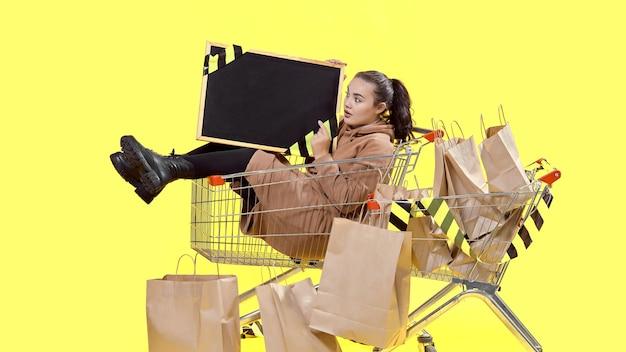 ブラックフライデー、女の子が買い物かごに座って、彼女の手でボードを驚かせて見る