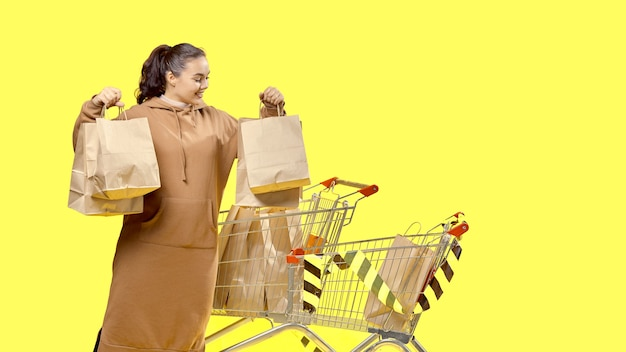 Черная пятница, девушка смотрит на свои сумки, стоя рядом с тележками для покупок.
