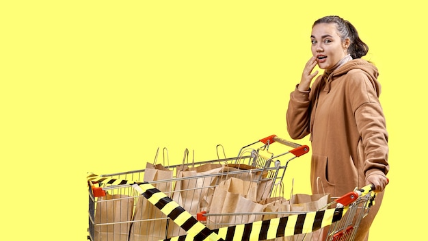 Черная пятница, девушка удивленно смотрит в камеру, стоя рядом с тележками супермаркета.