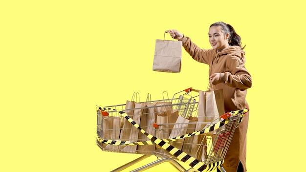 Черная пятница, девушка показывает пакеты с покупками, стоя рядом с тележками супермаркета