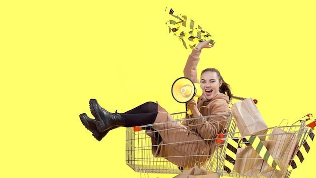 Черная пятница, девушка сидит в корзине с покупками и кричит в мегафон