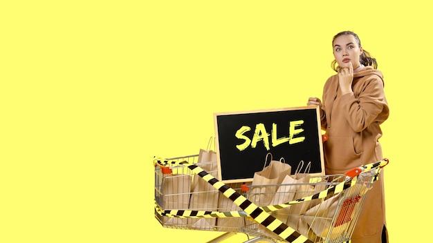 블랙 프라이데이, 쇼핑 카트에 서 있는 표지판 옆에 신중하게 서 있는 소녀