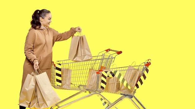 Черная пятница, девушка достает из тележки сумки с покупками