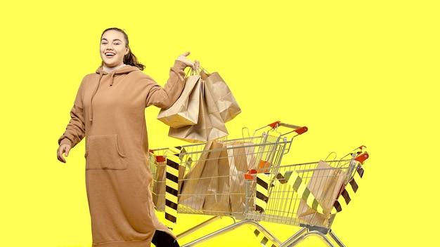 Черная пятница, счастливая девушка держит сумки с покупками, стоя рядом с тележками для покупок