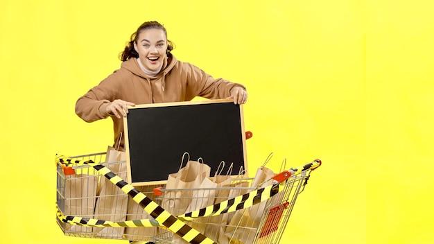 블랙 프라이데이, 행복한 소녀가 장바구니에 담긴 구매품 사이에 서 있는 표지판을 가리키고 있습니다