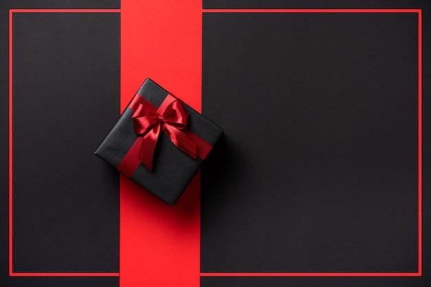 Черная пятница стильный темный подарок с бантом на темном фоне с местом для текста
