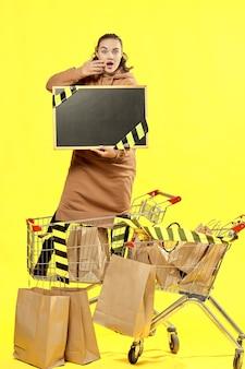 검은 금요일. 놀란 소녀는 쇼핑 카트에 복사할 곳이 있는 검은색 표지판을 들고 있습니다.