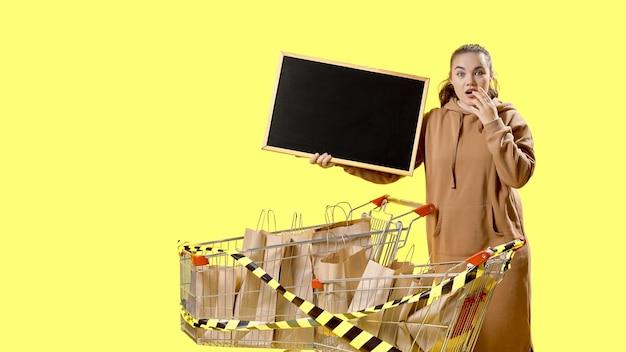 Черная пятница, удивленная девушка держит табличку рядом с тележками, заполненными сумками для покупок.