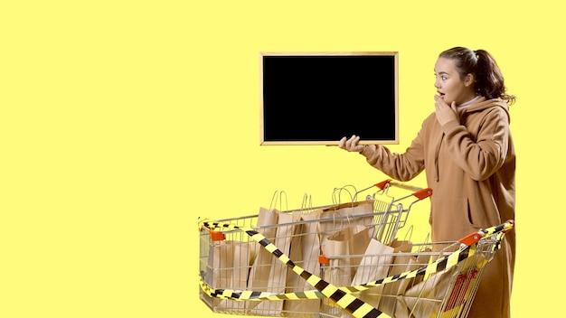 블랙 프라이데이, 놀란 소녀가 쇼핑백으로 가득 찬 카트 옆에 서서 표지판을 바라보고 있다
