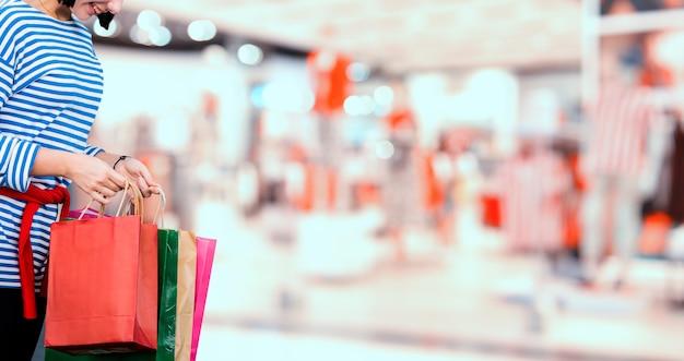 ブラックフライデーとボクシングデー。ショッピングギフトと休日のプレゼント。ショッピングバッグを持っているティーンエイジャーの女性。