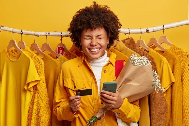 ブラックフライデーと販売コンセプト。大喜びの浅黒い肌の女性は巻き毛があり、広く笑顔で花束を持っています