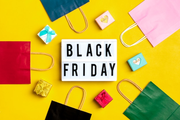 Black friday background with multi-colored packaging bags with gift boxes
