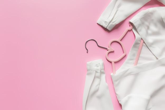 검은 금요일, 분홍색 배경에 의류 산업 개념은 분홍색 옷 걸이와 옷걸이에 하트 모양의 흰색 블라우스 드레스와 함께 누워