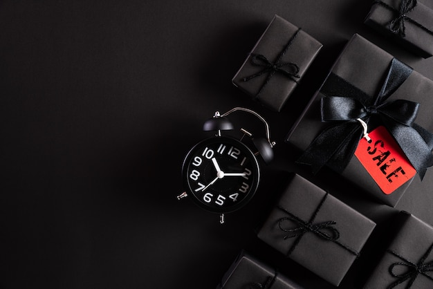Black friday composition   black gift box and alarm clock.