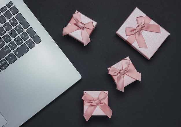 Black friday composition. laptop and gift boxes with bows on black background.