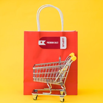 Black friday composition with cart in front of bag