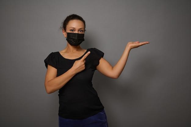 ブラックフライデーのコンセプト。黒の保護医療マスクの美しいブルネット混血の女性は、架空のコピースペースを保持し、人差し指でポイントし、カメラを見て微笑む