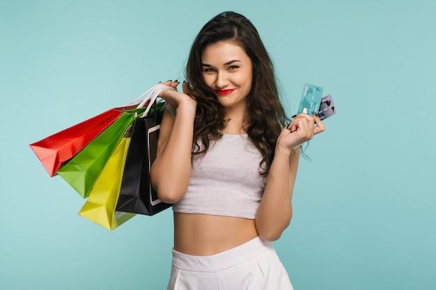 ブラックフライデーのコンセプト。クレジットカードと買い物袋を持って、カメラを見て、青い背景で隔離の幸せな若い美しい女性のクローズアップの肖像画
