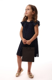 Black friday concept. isolated full-length portrait on white background with copy space of an adorable 4 years old child girl dressed in evening attire and golden shoes, holding a shopping packet.