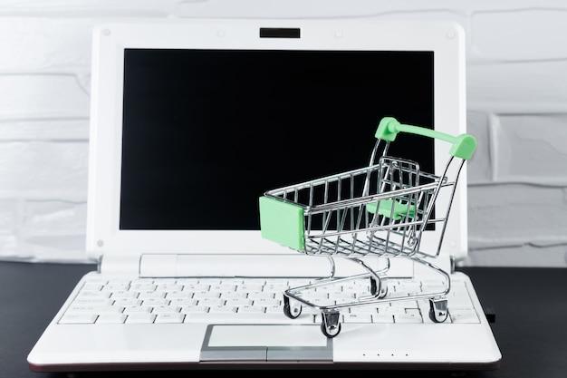 Концепция черной пятницы. мини-тележка для покупок и ноутбук. онлайн-продажа и скидки.