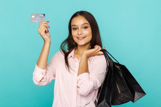 ブラックフライデーのコンセプト。孤立した黒いバッグとクレジットカードを保持しているきれいな女性。
